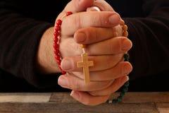 Verbindende Hände im Gebet mit Rosenkranzperlen Lizenzfreies Stockbild