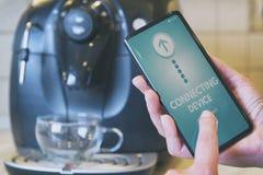 Verbindende koffiemachine met smartphone stock afbeelding