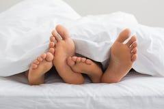 Verbindet die Füße, die heraus von unterhalb der Daunendecke haften Stockbild