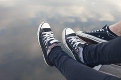 Verbindet Füße in den Turnschuhen, die durch das Wasser sich entspannen lizenzfreies stockfoto
