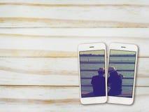 Verbindet Foto auf Smartphoneschirm auf Holz Stockbilder