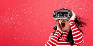 Verbindingen met vrouw die een virtuele werkelijkheidshoofdtelefoon met behulp van Stock Foto's
