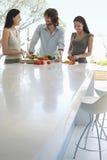 In Verbindung stehende Freunde bei der Zubereitung des Lebensmittels an der Küchenarbeitsplatte Stockbild