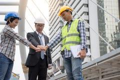 Verbindungshände des professionellen asiatischen Technikteams zusammen mit Stadthintergrund stockfoto