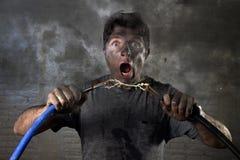 Verbindungskabel des ungeschulten Mannes, das elektrischen Unfall mit schmutzigem gebranntem Gesichtsschockausdruck erleidet Lizenzfreie Stockfotografie