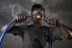 Verbindungskabel des ungeschulten Mannes, das elektrischen Unfall mit schmutzigem gebranntem Gesichtsschockausdruck erleidet Stockbild