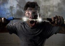 Verbindungskabel des ungeschulten Mannes, das elektrischen Unfall mit schmutzigem gebranntem Gesichtsschockausdruck erleidet Lizenzfreies Stockbild