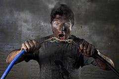 Verbindungskabel des ungeschulten Mannes, das elektrischen Unfall mit schmutzigem gebranntem Gesichtsschockausdruck erleidet Lizenzfreies Stockfoto