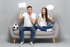 Verblüffte Paarfrauen-Mannfußballfane jubeln oben Stützlieblingsteam mit Sagenwolke des freien Raumes des Fußballgriffs leerer zu lizenzfreie stockfotografie