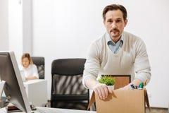 Verblüffter Manager, der den Kasten hält und im Büro sitzt Stockfotos