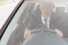 Verblüffter Mann, der am Steuer sitzt Lizenzfreies Stockfoto