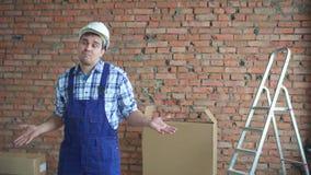 Verblüffter und verwirrter Mann in der Arbeitsuniform, die seine Arme wellenartig bewegt stock footage