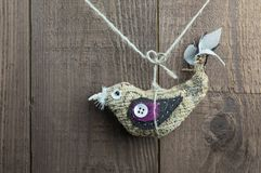 Verblaßte rustikale hängende Vogeldekoration auf einem hölzernen Hintergrund Stockbilder