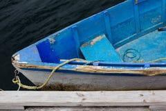 Verblaßtes blaues hölzernes Schlauchbootruderboot gebunden am Dock Stockfotografie
