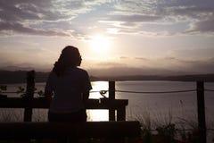Verblijf in eenzaamheid Een vrouw die op de zonneschijn in de avond zitten te letten royalty-vrije stock foto