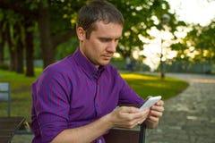 Verbonden het blijven Jonge mens het typen bericht op zijn mobiele telefoon royalty-vrije stock foto