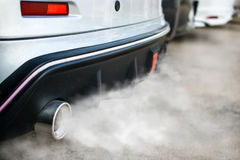 Verbrandingsdampen die auto uit uitlaatpijp komen Stock Foto