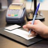 Verbraucher, der auf einem Verkaufsgeschäftsempfang unterzeichnet lizenzfreies stockfoto