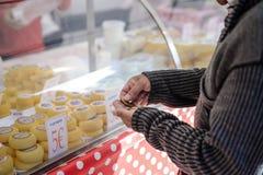 Verbraucher, der Münzen zählt, um Frischkäse zu kaufen Lizenzfreie Stockbilder