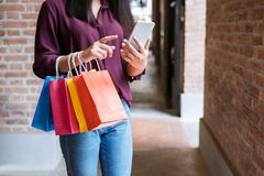 Verbraucherschutzbewegung, Einkaufen, Lebensstilkonzept, junge Frau, die bunte Einkaufstaschen und den Smartphone genießend im Ei lizenzfreie stockfotografie