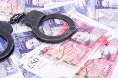 Verbrechen und Geld Die Handschellen sind auf den Pfund Lizenzfreie Stockfotos