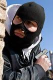 Verbrecher mit einem Gewehr, das auf ein Opfer wartet