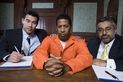 Verbrecher und Rechtsanwälte, die im Gerichtssaal sitzen stockfotografie