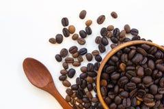 Verbreiten Sie Kaffeesamen auf dem hölzernen Löffel, der auf weißem Hintergrund lokalisiert wird Stockfotografie