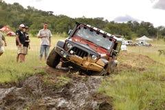 Verbrijzeling Beige Jeep Rubicon die modderhindernis kruisen stock afbeelding