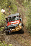 Verbrijzeling Oranje Jeep Rubicon die hindernis kruisen stock foto's