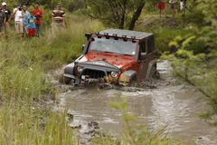 Verbrijzeling Oranje Jeep Rubicon die modderige vijver kruisen royalty-vrije stock foto's
