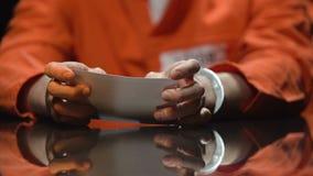 Verdacht in handcuffs die op foto letten, die met politie in onderzoek samenwerken stock footage