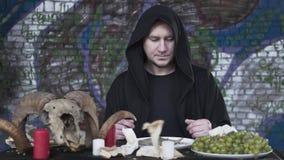 Verdachte mens in de zwarte kleren met de kap op de hoofdzitting bij de kleine lijst voor kaarsen, druiven stock video
