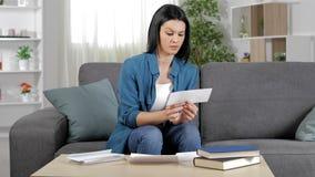 Verdachte vrouw die een ontvangstbewijs thuis lezen stock videobeelden
