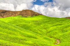 Verdant Green Mountains and Hills with Blue Sky and Rolling Clou Stock Images