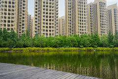 Verdant lakeshore in sunny modern city Stock Image