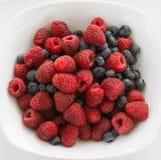Överdådiga hallon och blåbär i en vit maträtt Arkivfoton
