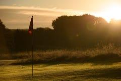 Verde de colocação do campo de golfe do nascer do sol, Autumn Dew na bandeira Imagens de Stock