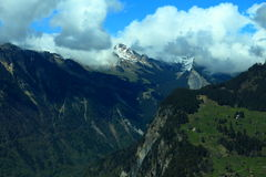 Verde de Murren, de Suíça e montanhas da neve com o céu azul nebuloso Imagens de Stock