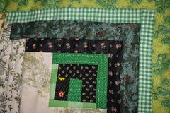 Verde del cuadrado del edredón de la cabaña de madera Imagen de archivo