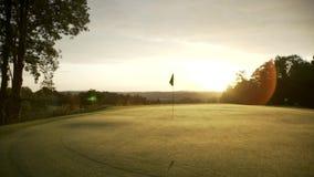 Verde del golf en la salida del sol de la mañana La bandera se está colocando en el verde mientras que el sol está subiendo en la