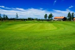 Verde del golf y casa del club Imagenes de archivo