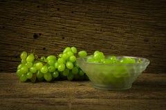 verde dell'uva con la ciotola su vecchio legno immagini stock libere da diritti