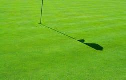 Verde di golf e un'ombra della bandierina fotografia stock