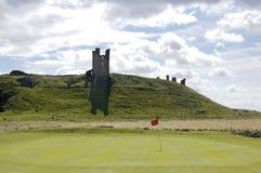 Verde do castelo e do golfe de Dunstanburgh Foto de Stock Royalty Free