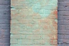 Verde e vermelho lavou a pintura em uma coluna do tijolo na cara de uma parede pintada roxo Foto de Stock Royalty Free