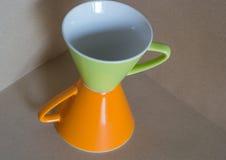 Verde en la taza anaranjada Imágenes de archivo libres de regalías