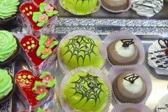Verde esmaltada, rojo y tortas de chocolate con las flores de la mermelada y el desmoche del chocolate imagen de archivo