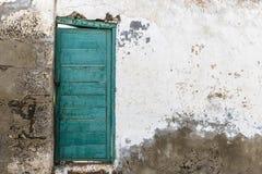 Verde a porta chiusa su una vecchia parete bianca rovinata Immagini Stock Libere da Diritti