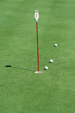 Verde que pone de la práctica con las pelotas de golf Foto de archivo libre de regalías